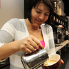 Albana Meta, owner of Gusto Cafe on Cabot St. in Beverly, pours steamed milk and foam on top of freshly brewed expresso to create a fun pattern for the top of her latte. David Le/Staff Photo