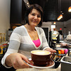 Albana Meta, owner of Gusto Cafe on Cabot St. in Beverly, displays a hot latte. David Le/Staff Photo