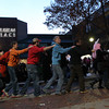 Halloween-goers near the Museum Place Mall form a congo line as they dance along with live music being played on Saturday evening.  David Le/Staff Photo