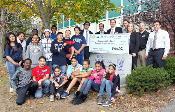 Brian Kelly, and representatives from Kelly Automotive, pose for a photo with members of the Higgins MIddle School Nighthawk Program, and the Greater Salem Boys and Girls Club, outside Higgins Middle School on Wednesday afternoon. David Le/Staff Photo