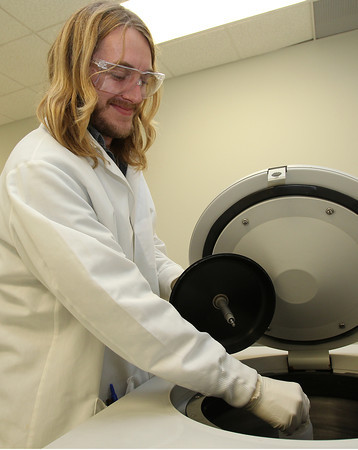 US Biological Biomanufacturing worker Justin Rendo pulls a bottle out of a centrifuge machine. David Le/Staff Photo