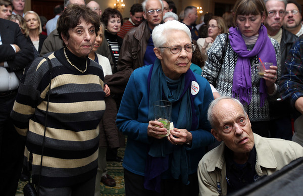 Marilyn Segal, left, of Marblehead, and Beverly and James Davies, of Beverly, intently watch the TV screen for poll results on Election Night at the John Tierney Headquarters at The Hawthorne Hotel. David Le/Staff Photo