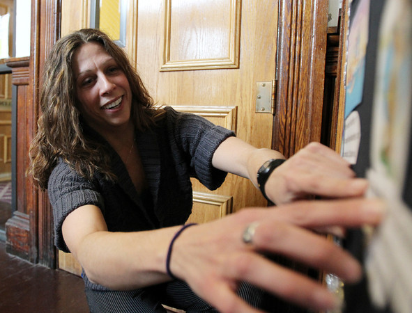 Lucia Delnegro hangs up some holiday decorations on the doors to her office in Peabody City Hall. David Le/Staff Photo