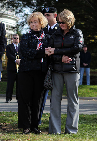 Jackie Raymond, right, and Agnes Raymond, left, mother and grandmother of fallen Swampscott soldier Jared Raymond, hold hands during a Veterans Day celebration dedicating a new memorial on Momument Ave on Sunday morning. David Le/Staff Photo