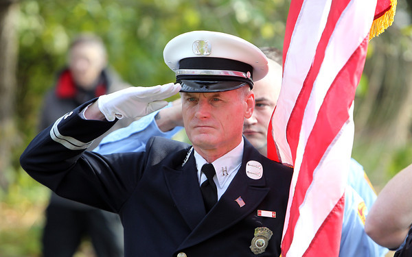 Swampscott fire captain Kevin Thompson salutes during the playing of the National Anthem on Sunday morning. David Le/Staff Photo
