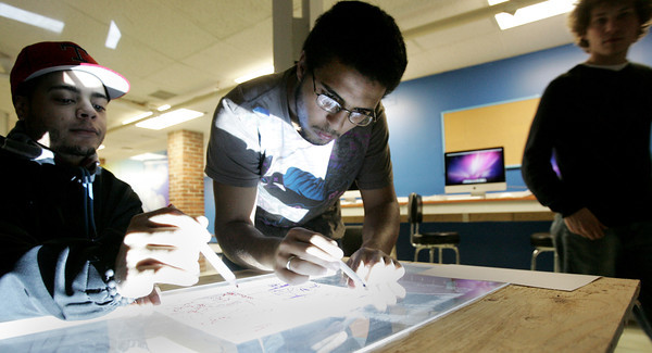 "Salem:<br /> Christian Matos, left, and Edwin Baez work on a ""invisible tracing table"" for a video project in the Salem YMCA's teen room. The room was recently renovated.<br /> Photo by Ken Yuszkus/The Salem News, Thursday, November 29, 2012."
