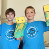 Phoenix School 5th graders Jack Custer, left, and Noah Dangora, right, display paper bag hand puppets they made at the Salem Indoor Farmer's Market. David Le/Staff Photo