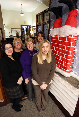 From left, Linda Bettencourt, Cindy Ransom, Mary Bonfanti, Laurie Duff, and Mary Codair, stand outside their decorated holiday door in Peabody City Hall on Wednesday afternoon. David Le/Staff Photo