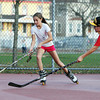 Madison Jalbert, 12, of Beverly, left, carries the ball upcourt while being defended by her brother Nick Jalbert, 14, right, while playing street hockey at the Balch Street Playground on Monday afternoon. David Le/Staff Photo