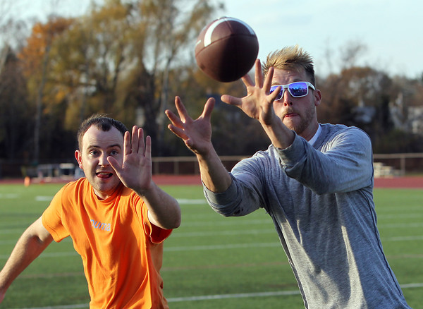 Andy Stone, right, of Middleton, catches a pass while being defended by Brian McDonald, also of Middleton, while playing pickup football at Beverly High School on Monday afternoon. David Le/Staff Photo