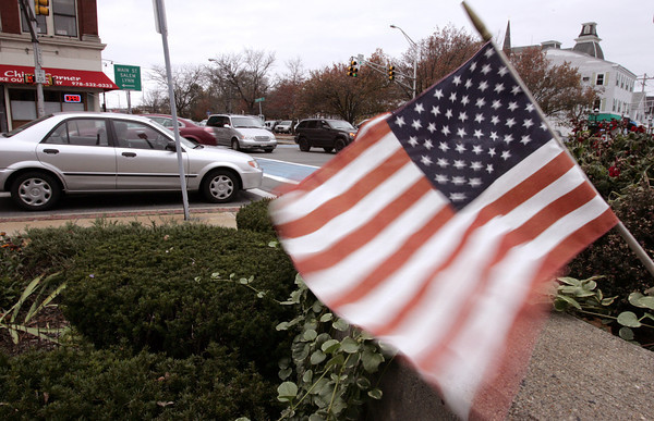 Peabody:<br /> A wind whipped flag is one of many small flags adorning Peabody center. The wind will continue into tomorrow along with occaissional strong gusts.<br /> Photo by Ken Yuszkus/The Salem News, Wednesday, November 7, 2012.