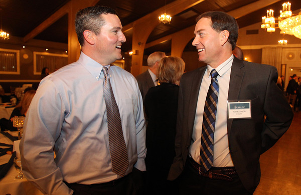 St. John's Prep 2012 Hall of Fame Inductee Todd Buckley, right, talks with Dale Kimball, left, at the Danversport Yacht Club on Wednesday evening. David Le/Staff Photo