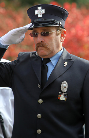 Swampscott firefighter Ed Seligman salutes during a Veterans Day memorial dedication on Momument Ave in Swampscott on Sunday morning. David Le/Staff Photo