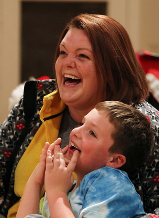 Erin Cullen and her son Alex, 7, of Hamilton, laugh and sing along to Dominick the Christmas Donkey at the Hamilton-Wenham Community House Annual Caroling and Tree Lighting Festivities on Thursday evening. David Le/Staff Photo