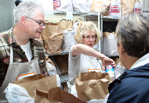 Mark Paluzzi, left, and Jan Kinkopf, right, pack up food for clients at Beverly Bootstraps on Tuesday evening as they gave out food for the Thanksgiving Holiday. David Le/Staff Photo