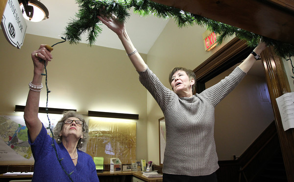 Estelle Clark, right, and Pauline Hudson, left, of the Peabody City Hall Assessors Office hang up lights around the window frame to their office on Wednesday afternoon. David Le/Staff Photo