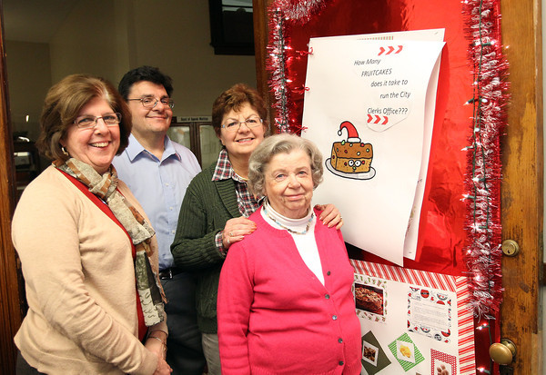 From left, Marilyn Limongiello, Peabody City Clerk Tim Spanos, Colleen Kolodziej, and Irene Zielski, stand in front of their holiday decorated door on Wednesday afternoon. David Le/Staff Photo