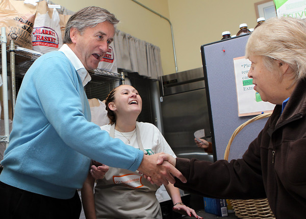 Nancy Stewart, right, shakes hands with Congressman John Tierney, left, at Beverly Bootstraps on Tuesday while picking up Thanksgiving supplies on Tuesday evening. David Le/Staff Photo