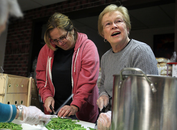 Mary Ann Zampell, left, and Alana Madden, smile as they prepare green beans for a Thanksgiving meal for those in need at Ma Duke's in Danvers on Wednesday evening. David Le/Staff Photo