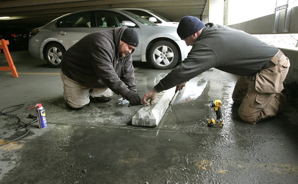 Salem:<br /> Richardo Vega, left, and Paul Kennedy prepare the parking spaces for four new electric vehicle charging stations on the 2nd floor of the Museum Place Mall parking garage. Also, four more stations are going in the South Harbor Garage.<br /> Photo by Ken Yuszkus/The Salem News, Wednesday, November 28, 2012.