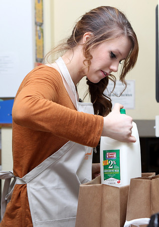 Beverly High School junior Gina De Matteo packs bags of groceries for clients at Beverly Bootstraps on Tuesday evening as many families stopped by to pick up food supplies for Thanksgiving. David Le/Staff Photo