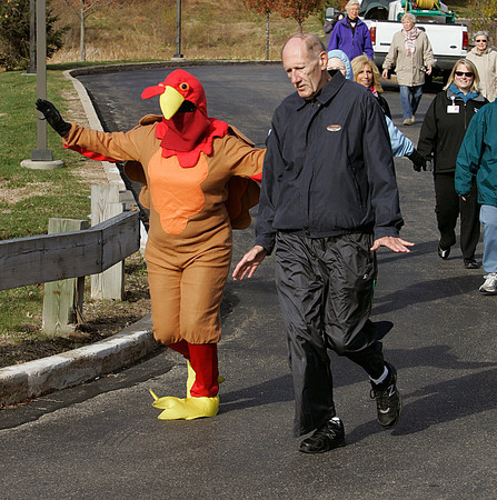 Peabody:<br /> A turkey and John Wroblewski, right, flap their arms as they lead the group of residents at Brooksby Village who are participating in the Turkey Trot around the grounds of Brooksby Village.<br /> Photo by Ken Yuszkus/The Salem News, Friday, November 16, 2012.