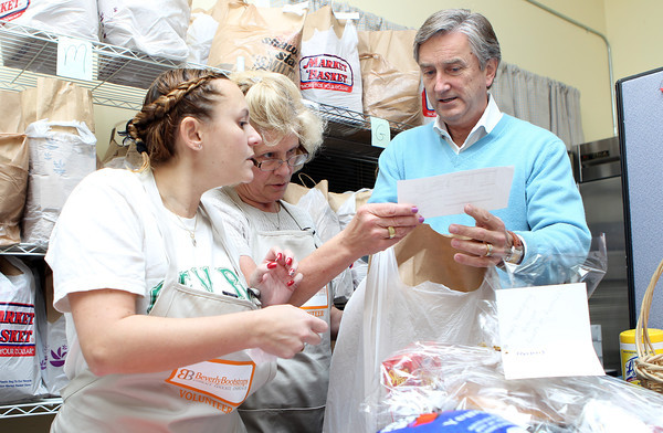 From left, Sherry Zide, Jan Kinkopf, and Congressman John Tierney review a list of supplies being given out to families at Beverly Bootstraps on Tuesday evening for the Thanksgiving Holiday. David Le/Staff Photo