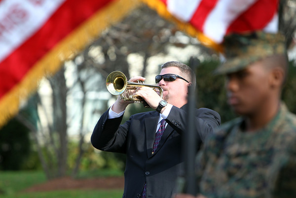 """Swampscott Band Director Scott Winship plays """"Taps"""" at a memorial dedication on Monumet Ave in Swampscott on Sunday morning. David Le/Staff Photo"""