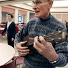 Peabody:<br /> Dan McDuffie plays the baratone ukelele as Barbara Therrien teaches the men how to hula dance for the upcoming Forever Young Chorus music program. <br /> Photo by Ken Yuszkus/The Salem News, Thursday, November 8, 2012.