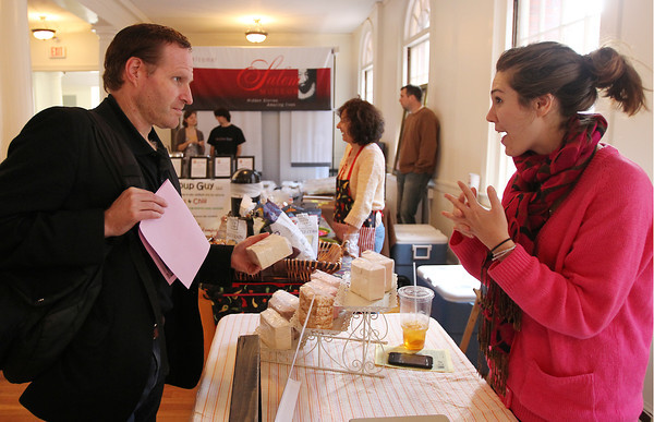 Paul Bremer, left, of Rockport, talks with Sarah Pike, right, of Sweet Lydia's in Lowell at the Salem Winter Farmer's Market on Thursday afternoon inside Old Town Hall. David Le/Staff Photo