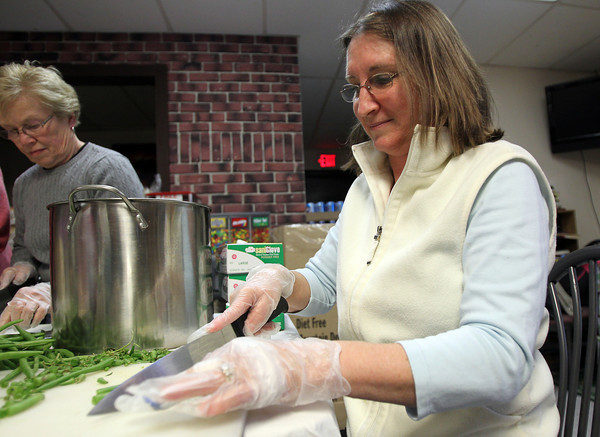 Deb Wilson prepares green beans for a Thanksgiving meal for those in need at Ma Duke's on Wednesday evening. Ma Duke's is preparing 120 turkeys, 40 hams, and over 500 pounds of potatoes along with side dishes. David Le/Staff Photo