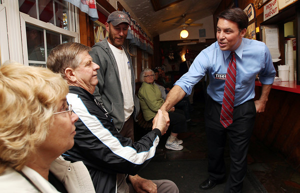 US Congress candidate Richard Tisei, right, shakes hands with Paul and Jane Barrett, left, of Danvers on Thursday afternoon while campaigning at The Clam Box in Ipswich. David Le/Staff Photo