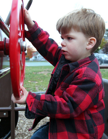 Nate Skuse, 2 1/2, of Beverly, pretends to drive a car on the playground at Kimball Haskell Park on Thursday afternoon. David Le/Staff Photo