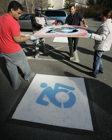 Wenham:<br /> From left, Matthew Mckoy, Gregory Geffrard, Brian Glenney, Maria Muir lift off a stencil after spray painting the new logo on one ot the parking spaces at Gordon College. Gordon has updated its handicapped parking signs with a new logo designed by college's assistant professor Brian Glenney. All except Brian Glenney are from the Beverly Triangle Group. <br /> Photo by Ken Yuszkus/The Salem News, Monday, November 19, 2012.
