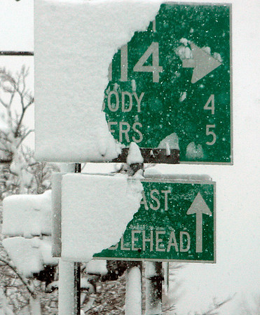 Salem: Directional signs in Salem are partly covered with snow, during the first major snow fall of 2011. Photo by Mark Lorenz/Salem News