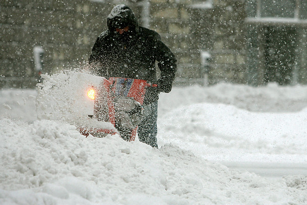 Salem: A worker clears snow from the sidewalk at the corner of Church and Washington Street in Salem, during the first major snow fall of 2011. Photo by Mark Lorenz/Salem News