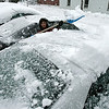 Beverly: Michelle Brooks clears off her roommates car off of Water Street in Beverly. Michelle took the day off from her work, she works in Boston. Photo by Mark Lorenz/Salem News