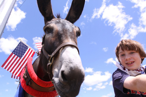 Colby Jacques prepares to lead his donkey, Mary, in the 4th of July parade at Brooksby Village retirement community on Friday. The parade was held two days early for Brooksby Village, the nice weather drew out a large crowd of spectators. Photo by Cole Margen/ Salem News.