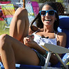 Kristine Kapoll of Danvers catches some sun and chats with her friends while waiting for festivities to start at the Danvers Fireworks Festival on Saturday afternoon at Plains Park in Danvers. Photo by David Le/Salem News