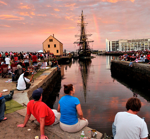 Andrew Sheehan and Danielle Blais, both from Salem , sit at the waters edge along with large crowds to celebrate the 4th of July in Salem at the Salem Maritime National Historic Site as a rainbow comes out at dusk.   Photo by Mark Teiwes / Salem News