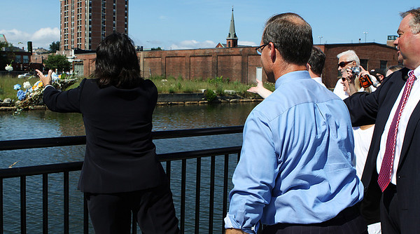 From left, Salem Mayor Kimberly Driscoll, state Rep. John Keenan and Salem Ward One Councilor Bob McCarthy toss a ceremonial wreath into the South River as part of the convocation ceremony for the Harborwalk, which runs between Lafayette and Congress Streets. Photo by David Le/Salem News