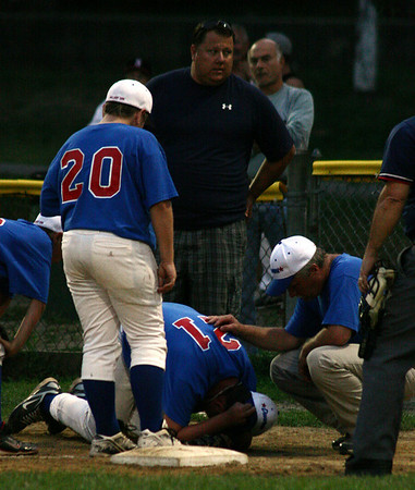 Salem: Danvers first baseman Corey Crossley reacts after hitting a Swampscott runner's hip with his head as he ran for the ball at first base. Crossley recovered a few moments later and continued to play in the game. Photo by Mary Catherine Adams/Salem News.