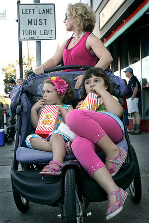Danvers: Josephina Montevecchi, 2, at left, and her sister Lilliana, 5, munch on popcorn while they and their mother Gabrielle watch people dance during Oldies Night at the Danvers Family Festival on Wednesday. Photo by Mary Catherine Adams/Salem News