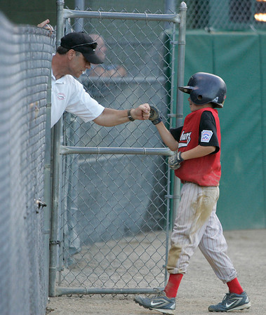 Peabody: Chris Francoeur gets a fist bump from Amesbury's team manager, Peter Dodier, after scoring a run early in the District 15 little league winner's bracket final. Photo by Mary Catherine Adams/Salem News.