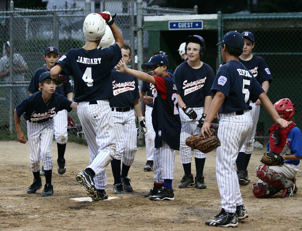 Salem: Swampscott's Ryan January gets high fives from his teammates as he crosses home plate after hitting a home run in the fourth inning. Photo by Mary Catherine Adams/Salem News.