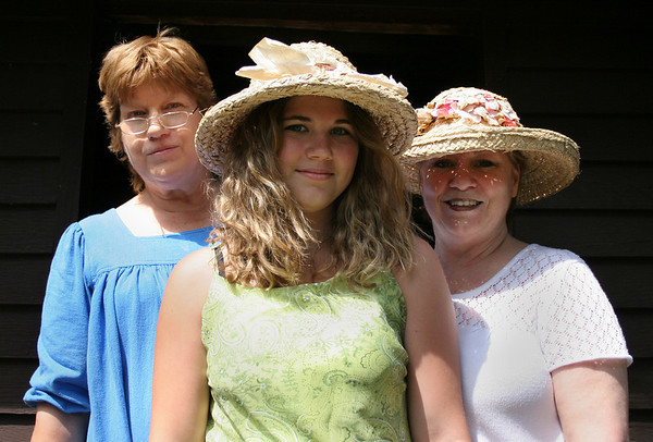 Topsfield: Meg Philpott, of the Topsfield Historial Society, left, Sam LaRue, 14, and Irene O'Neill, stand just outside the Parson Capen House. Guests were invited to wear straw hats to the historical society's afternoon tea on Wednesday, July 28. Photo by Mary Catherine Adams/Salem News.