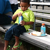 Salem: Jayden Santos, 3, opens a can of Sprite after taking a bite from a hot dog grilled by Salem police's community impact unit. Photo by Mary Catherine Adams/Salem News.<br /> , Salem: Jayden Santos, 3, opens a can of Sprite after taking a bite from a hot dog grilled by Salem police's community impact unit. Photo by Mary Catherine Adams/Salem News.
