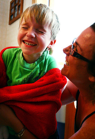 "Peabody: Hunter Jorgenson, 5, laughs as his mother, Tracey, coaxes him out of hiding behind his blanket. The younger Jorgenson appeared in the movie ""Knight and Day"" with Tom Cruise. Photo by Mary Catherine Adams/Salem News"