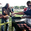 Salem: Salem police Sgt. Harry Rocheville, far right, and patrolman Robert Phelan serve hamburgers to Mishel Guerro, far left, and Juan Guerrero. The Salem police community impact unit hosted a cookout for kids in the Point neighborhood at Palmer Cove Park on Wednesday evening. Photo by Mary Catherine Adams/Salem News.<br /> , Salem: Salem police Sgt. Harry Rocheville, far right, and patrolman Robert Phelan serve hamburgers to Mishel Guerro, far left, and Juan Guerrero. The Salem police community impact unit hosted a cookout for kids in the Point neighborhood at Palmer Cove Park on Wednesday evening. Photo by Mary Catherine Adams/Salem News.