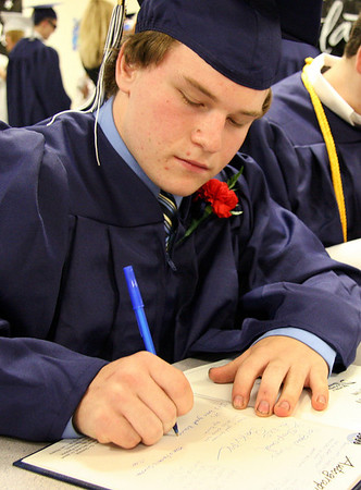 Middleton: Craig Slazenik signs a yearbook before the graduation ceremony starts at North Shore Technical High School on Friday. Photo by Mary Catherine Adams/Salem News<br /> , Middleton: Craig Slazenik signs a yearbook before the graduation ceremony starts at North Shore Technical High School on Friday. Photo by Mary Catherine Adams/Salem News
